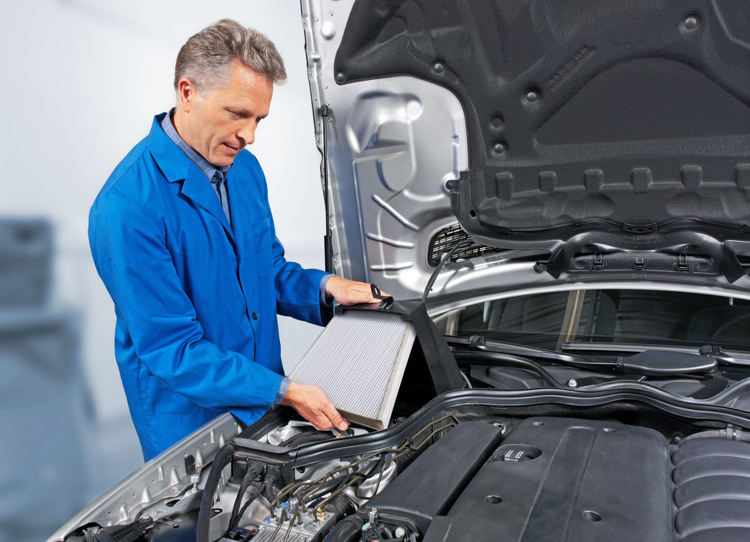 Mecaniker tauscht den Innenraumfilter der Autoklimaanlage