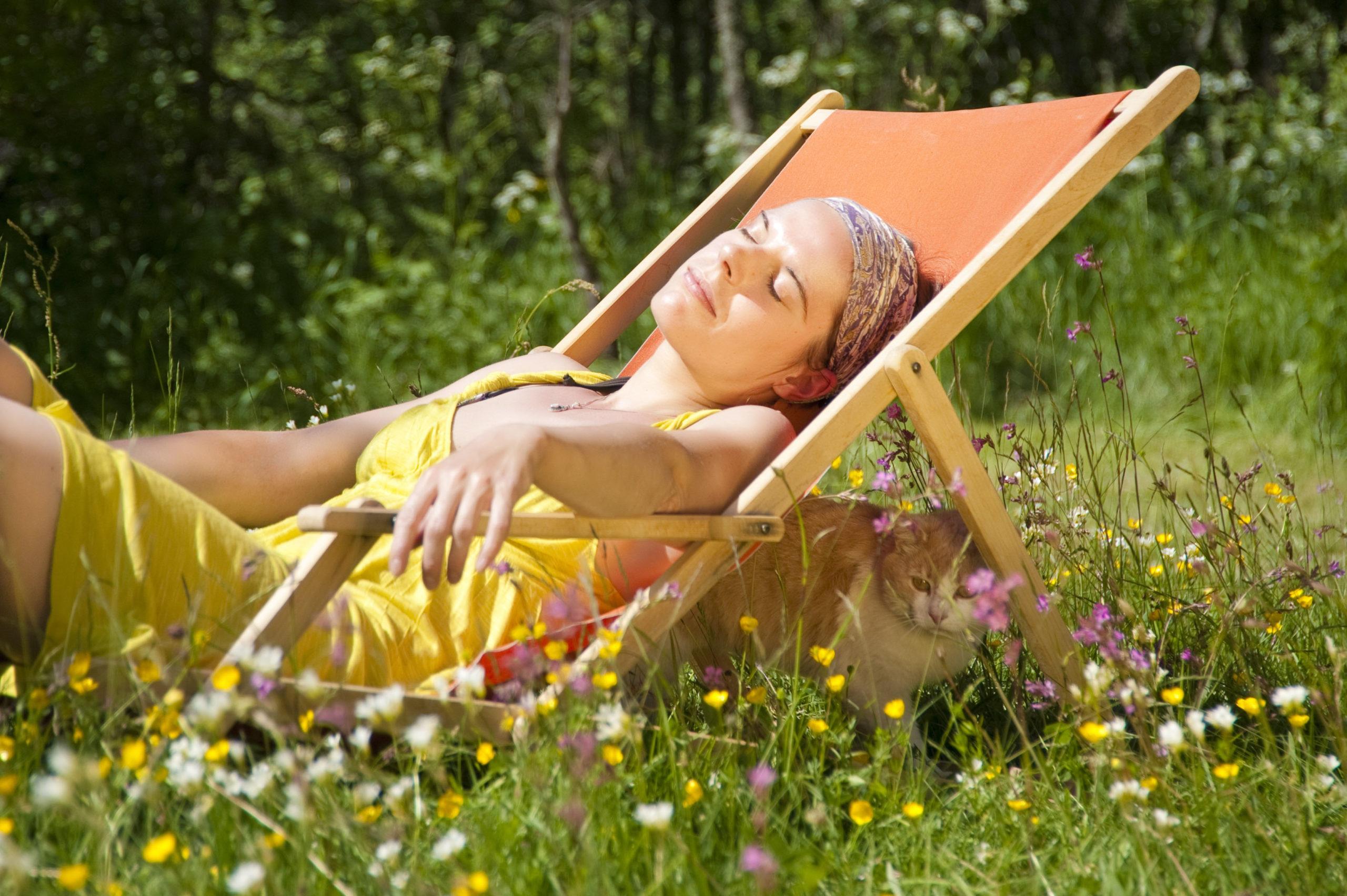Frau im Sonnenstuhl auf einer Wiese - Probiotika gegen Heuschnupfen