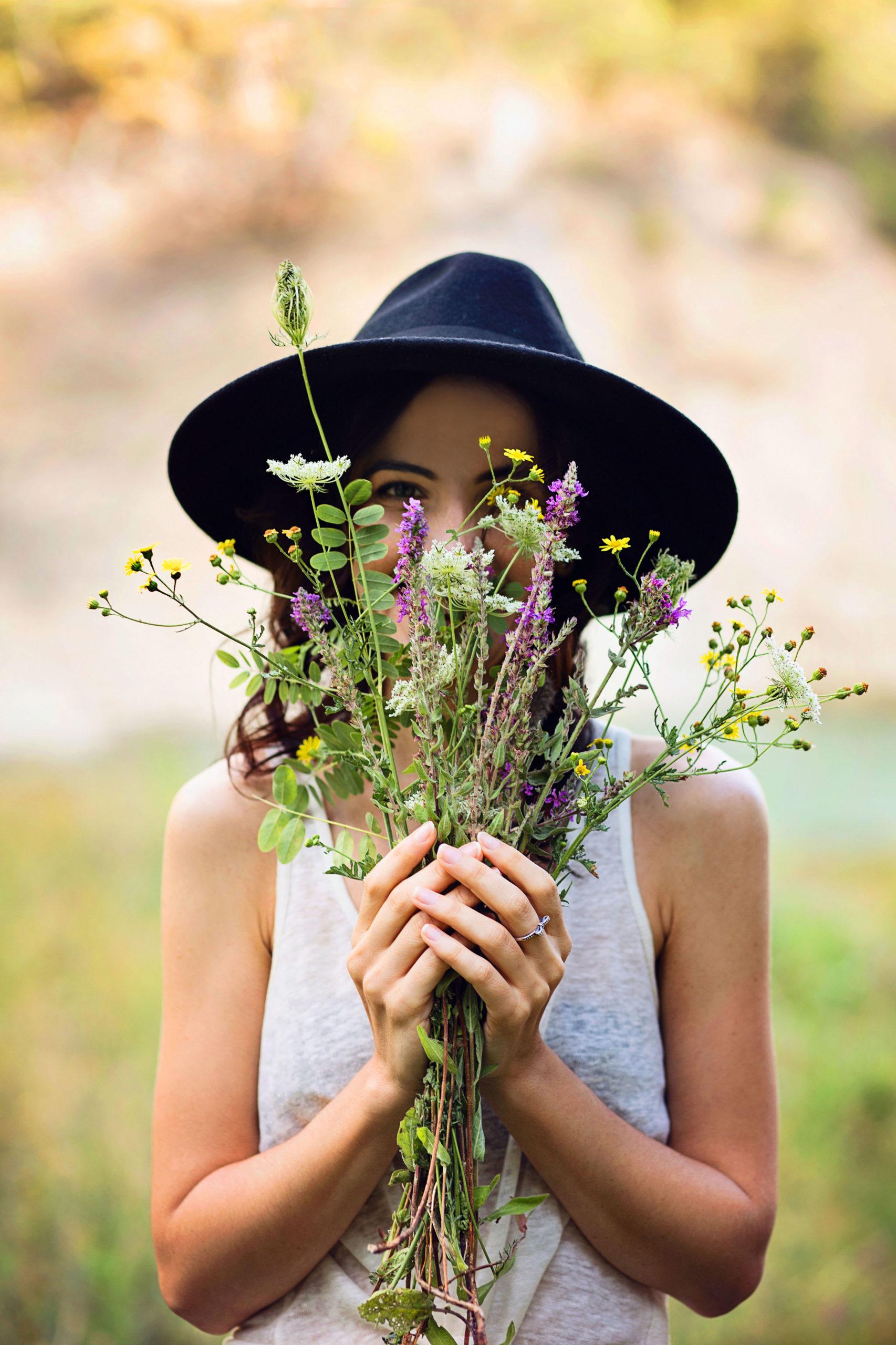 Junge Frau schaut durch einen Blumenstrauss - Probiotika gegen Heuschnupfen